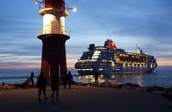 Kreuzfahrtschiff beim Auslaufen aus Warnemünde am Abend